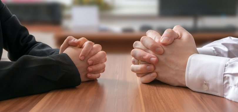 a picture of two folded pairs of hands across from each other discussing salary in an interview